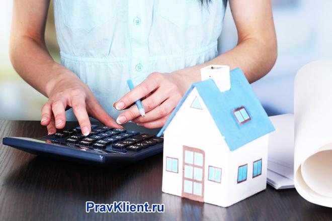 Девушка в голубой блузке считает на калькуляторе, рядом стоит бумажный домик