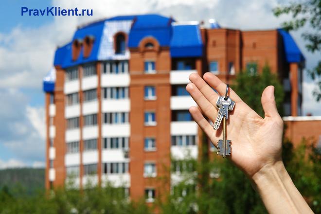 Девушка держит в руке ключи на фоне многоэтажного дома