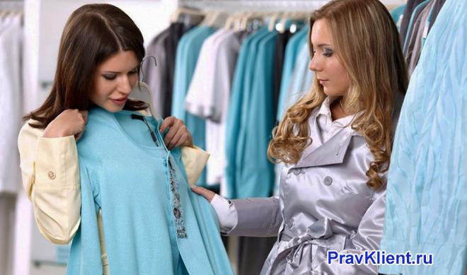 Девушка выбирает кофточку в магазине