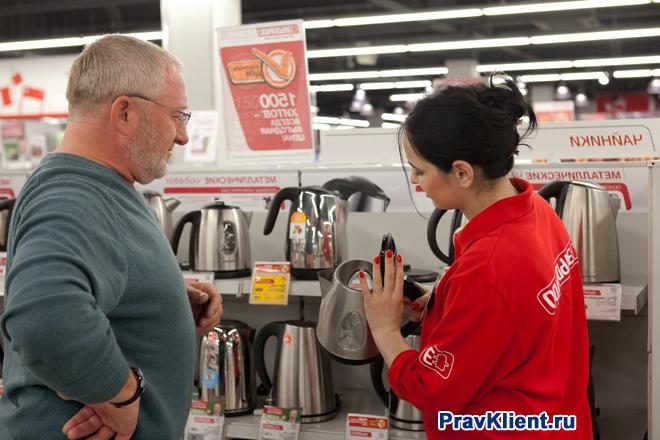 Продавец-консультант показывает мужчине чайник с витрины
