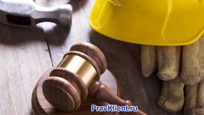 Строительная каска, перчатки и деревянный молоточек