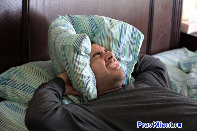 Мужчина закрывает уши подушкой