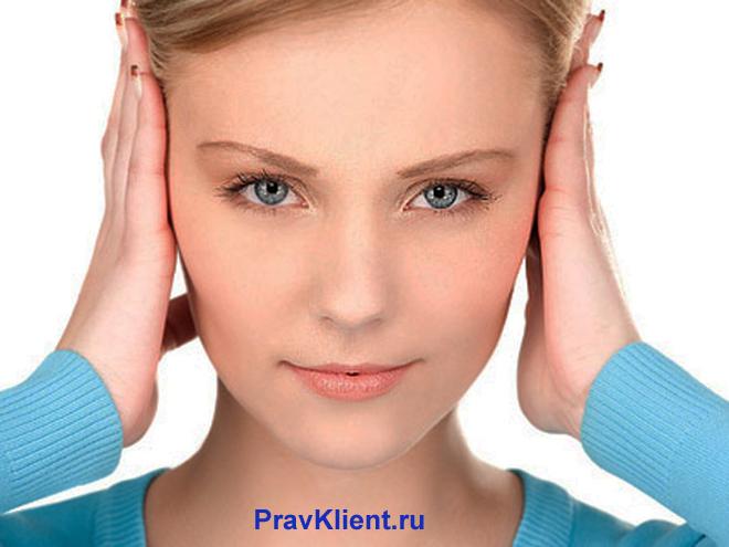 Девушка прикрывает уши руками