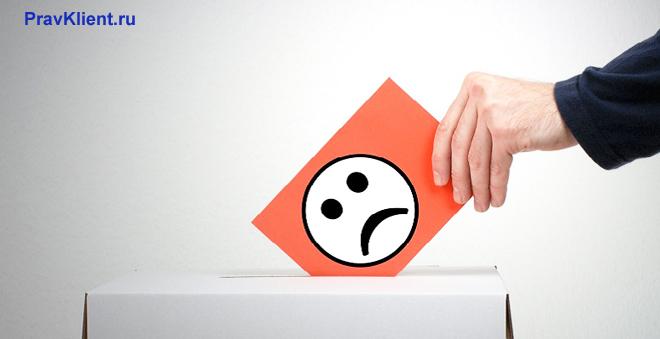 Мужчина кидает в урну конверт с расстроенным смайлом