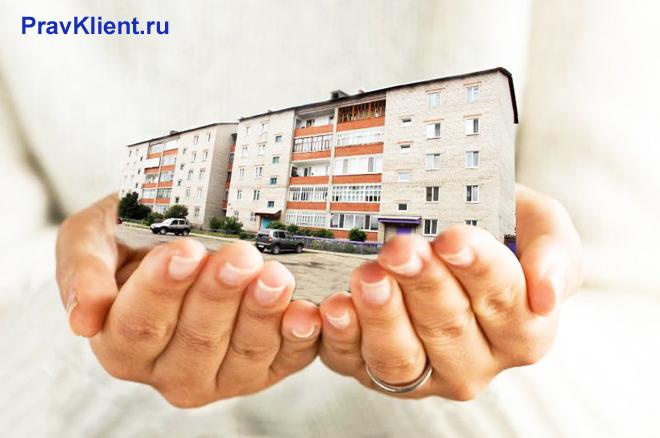 Человек держит в руках многоэтажный дом