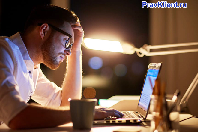 Бизнесмен работает за ноутбуком ночью