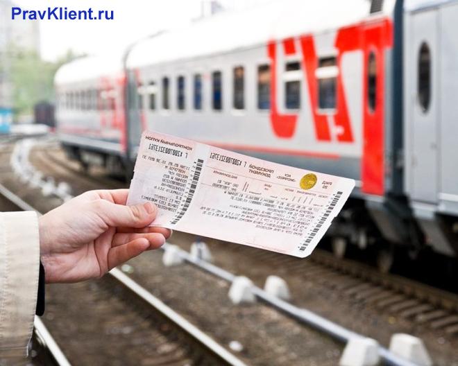 Пассажир держит в руке билет на поезд