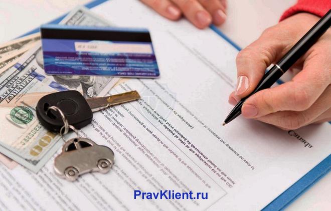 Мужчина расписывается в документах, рядом лежат банковская карточка и ключи с брелком в виде машинки