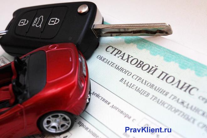 Страховой полис, красная машина, ключи с сигнализацией