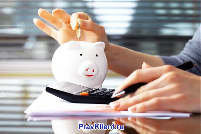 Девушка ведет расчеты на калькуляторе и кидает монетки в копилку