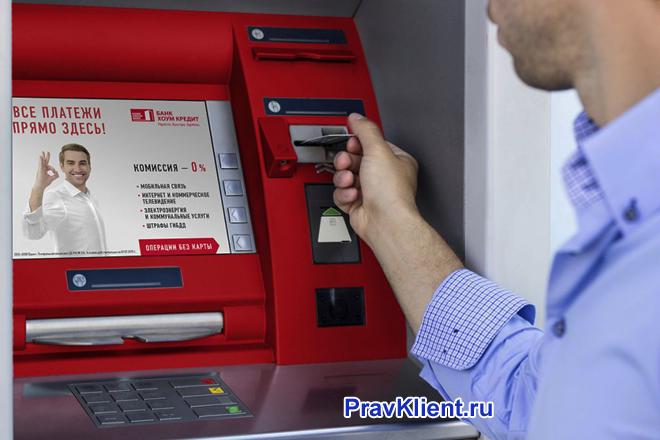 Мужчина пользуется банкоматом Хоум кредит банка