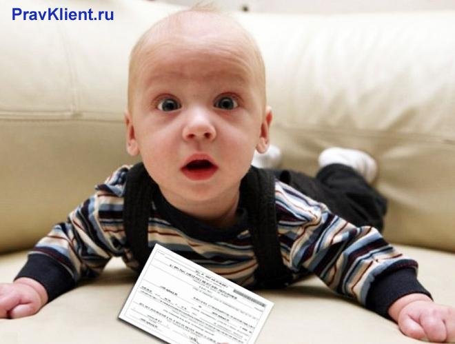 Грудной ребенком лежит на диване, рядом с ним документ
