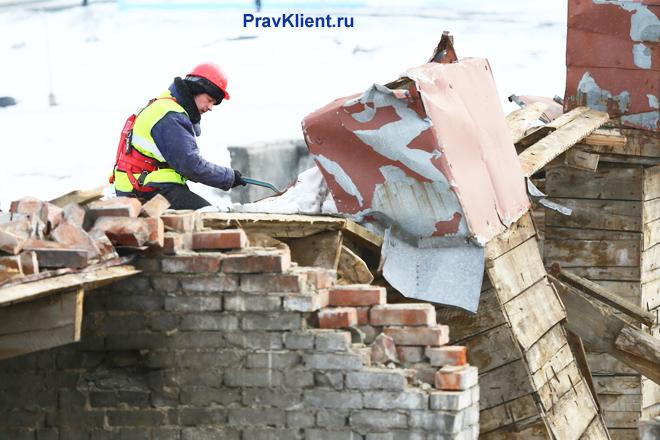 Рабочий и разрушенные стены