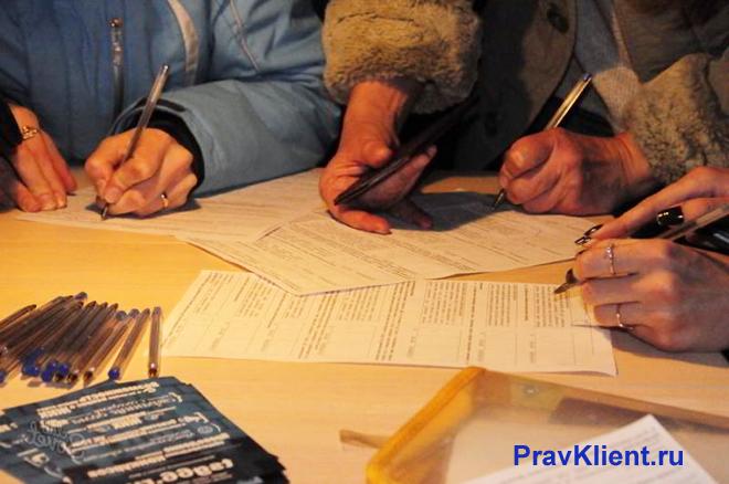 Люди за общим столом пишут заявление