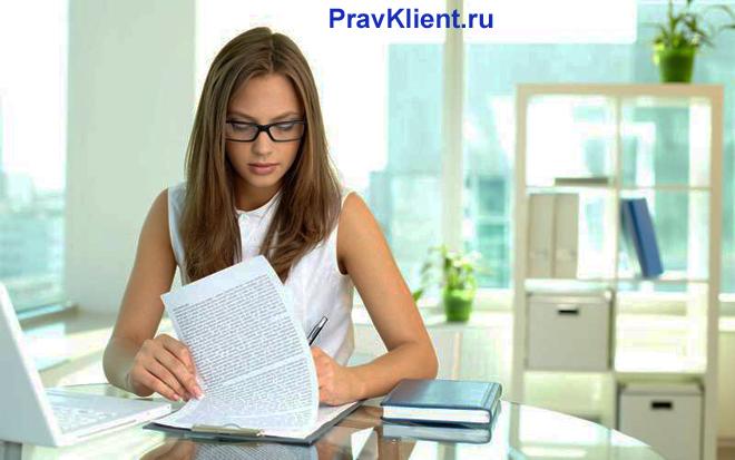 Девушка читает в офисе бумаги
