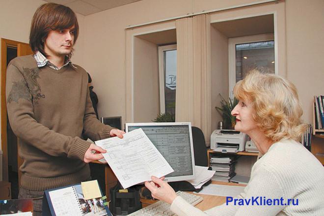 Мужчина протягивает заявление женщине за компьютером