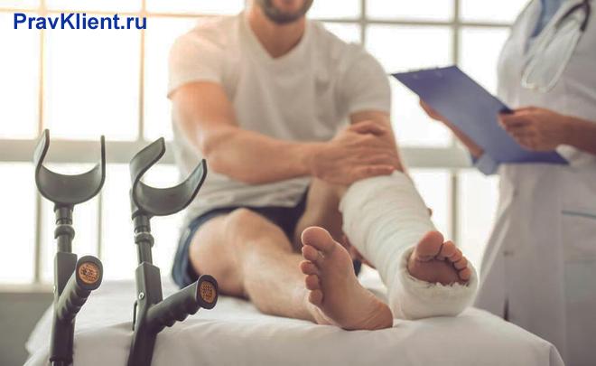 Мужчину с поврежденной ногой осматривает врач