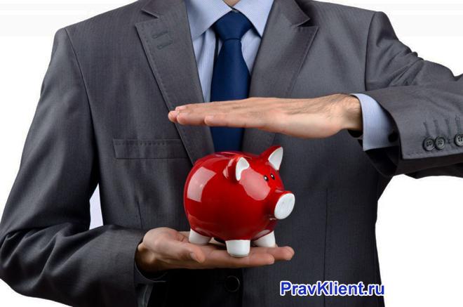 Бизнесмен держит в руках красную копилку-хрюшку