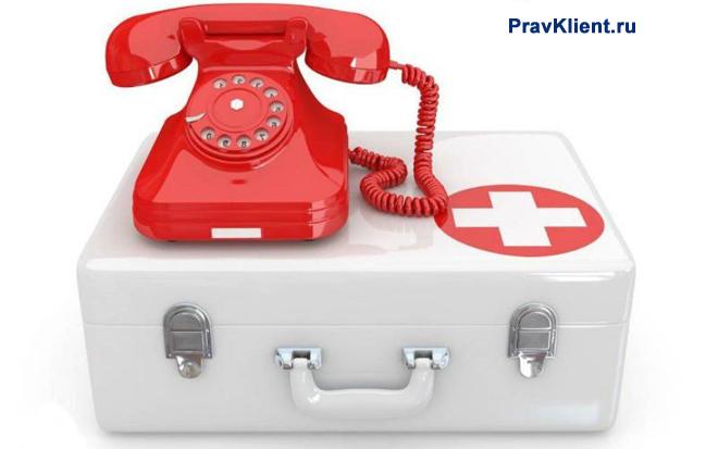 Красный телефон стоит на аптечке