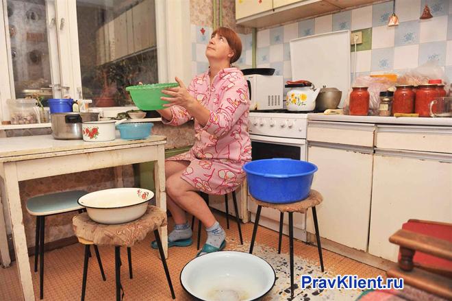 Девушка расставила тазики на кухне, с потолка капает вода