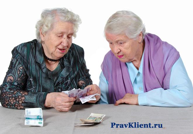 Две старушки считают деньги за столом