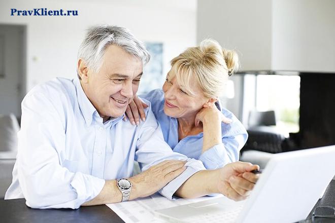 Муж работает за ноутбуком, рядом с ним жена