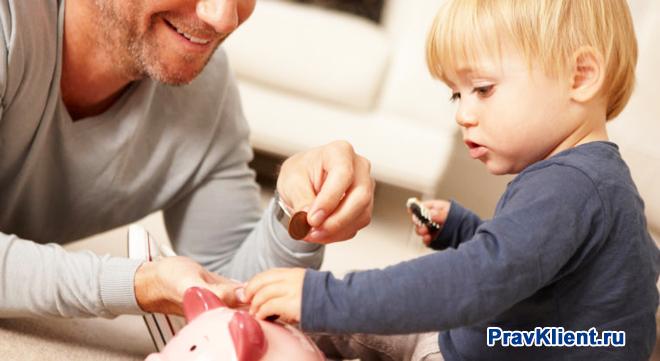 Папа и сын кидают монетки в копилку