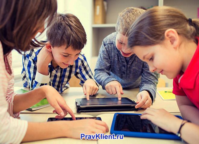 Дети сидят вместе за столом и играют в планшетах