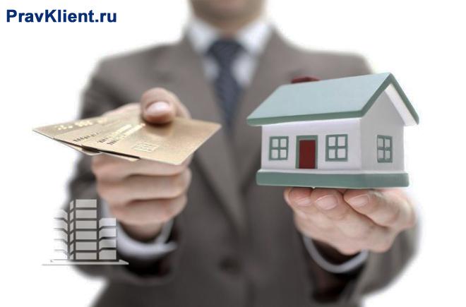 Бизнесмен держит в руках домик и банковскую карточку