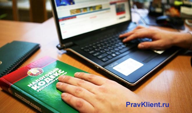 Мужчина за ноутбуком, рядом лежит Налоговый кодекс РФ