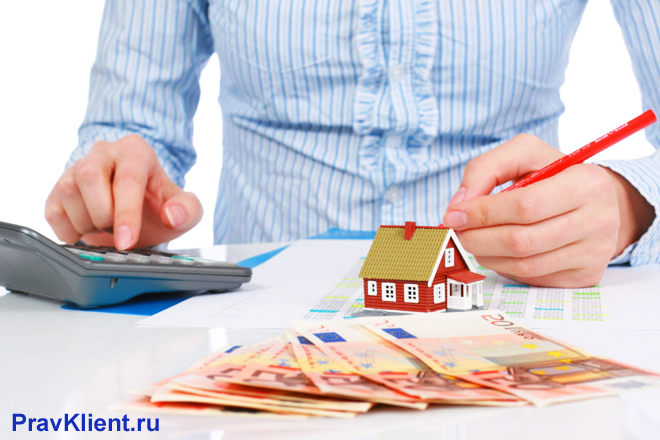 Мужчина в голубой рубашке считает деньги за дом на калькуляторе