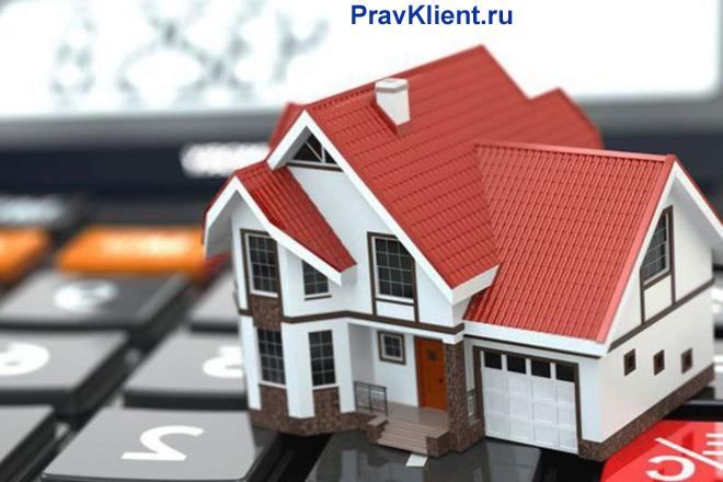 Дом с красной крышей стоит на клавишах калькулятора