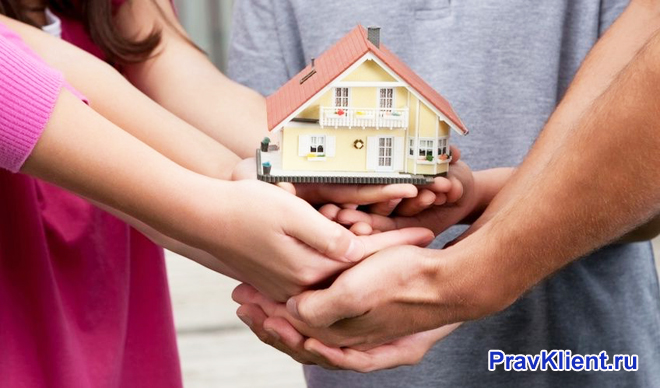 Семья держит в руках дом