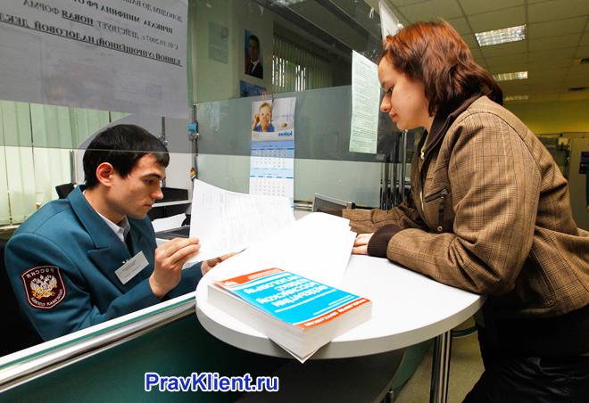 Девушка подает декларации в налоговую инспекцию