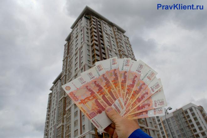 Мужчина держит в руке веер из денег на фоне высотного здания