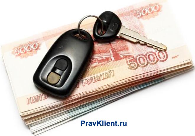 Ключи с сигнализацией лежат на пачке денег