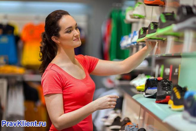 Продавец раскладывает кроссовки на витрине