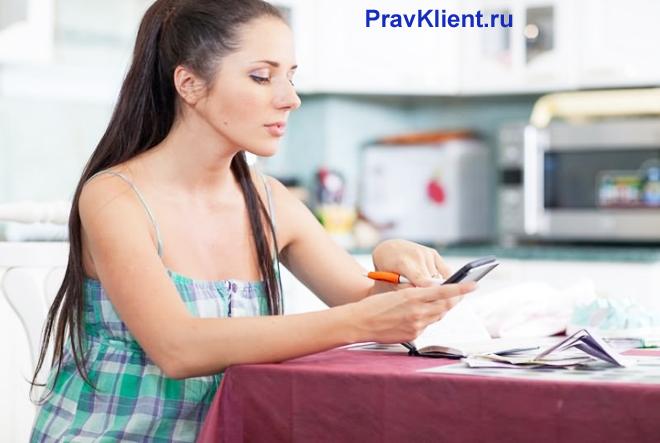 Девушка сидит за столом на кухне и читает документы