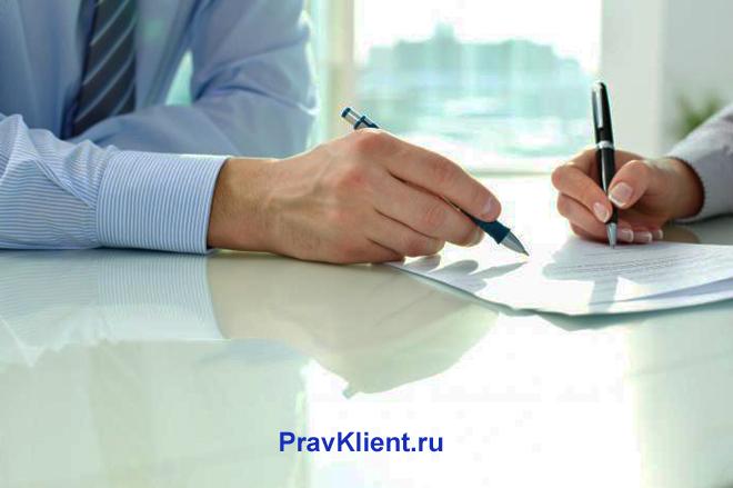 Бизнесмены за столом общаются насчет документов