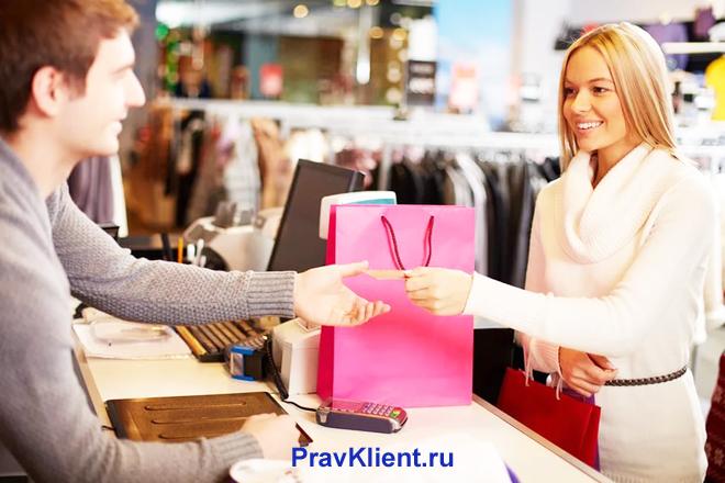 Девушка расплачивается за покупки на кассе в магазине одежды