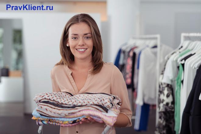Продавец одежды раскладывает товар