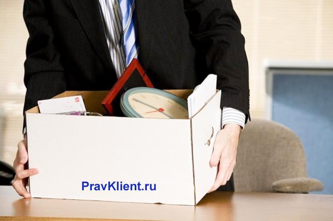 Бизнесмен держит в руках коробку с личными вещами