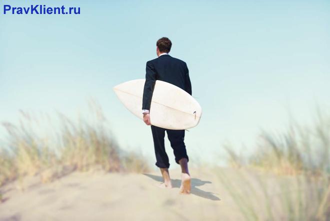 Офисный работник гуляет по берегу моря