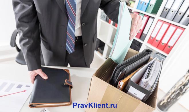 Бизнесмен собирает папки в коробку