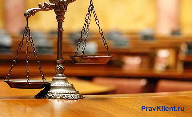 Весы на фоне зала судебных заседаний