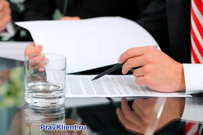 Мужчина за зеркальным столом подписывает документы