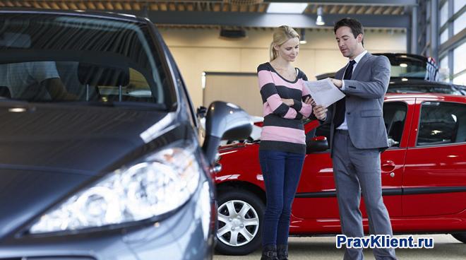 Продавец отдает документы в руки покупательнице автомобиля