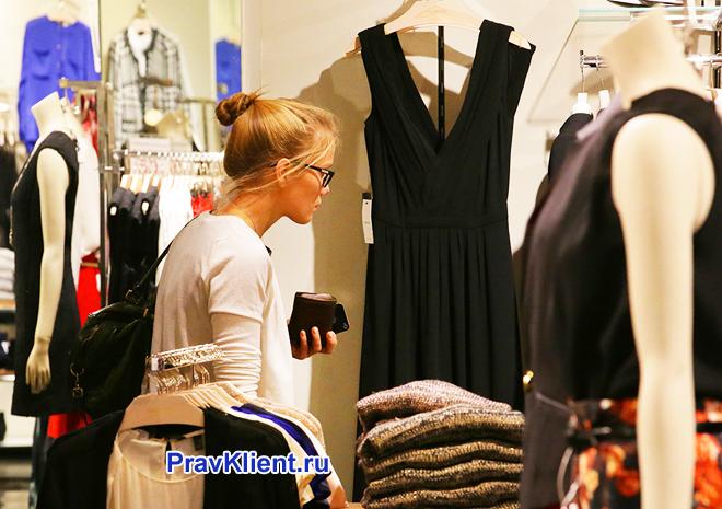 Покупательница рассматривает черное платье в магазине одежды