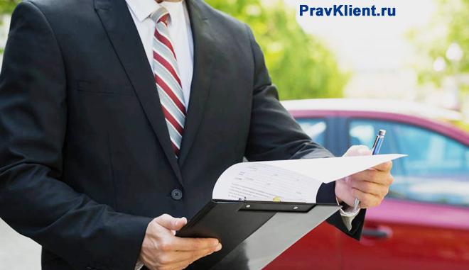 Бизнесмен стоит с папкой на фоне автомобиля