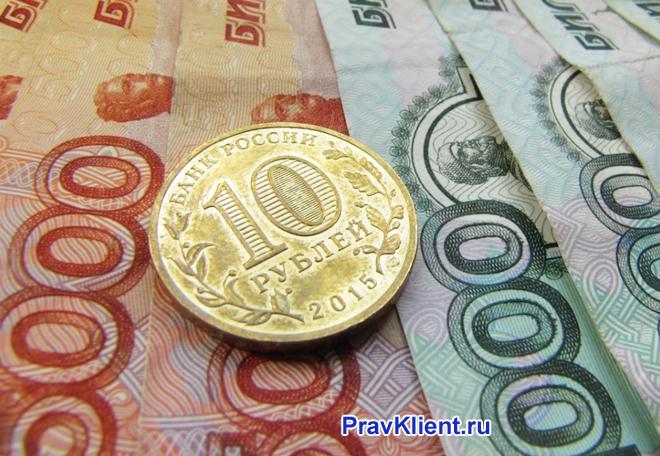 Денежные купюры и золотая монетка